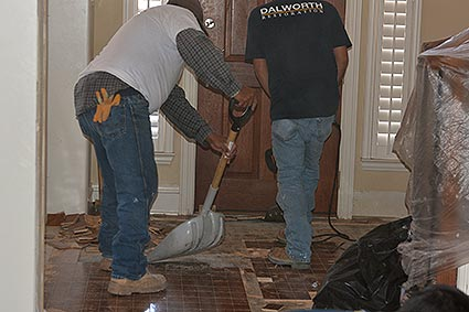 Dalworth Restoration crew members remove water damaged hardwood flooring from home in Frisco, TX.