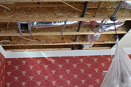 A portion of the ceiling removed due to water damage from an upstairs toilet overflow.