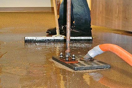 Dalworth technician using a water claw to extract water from flooring