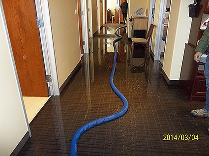 Removing water from a flooded hallway at a hospital