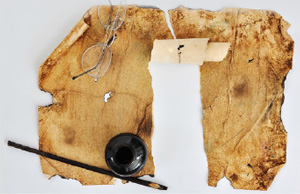 an old tattered piece of parchment paper with glasses and restoration tools resting nearby