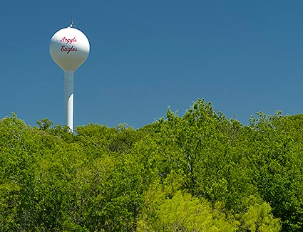 The Argyle, TX water tower surrounded by rolling hills and a beautifully green environment.