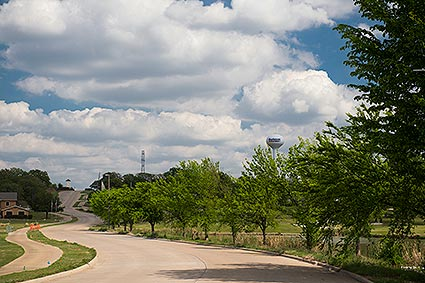 A water tower past acres of rolling hills and a green environment in Burleson, TX.