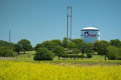 The Denton, TX water tower is surrounded by beautifully aesthetic green evironment.