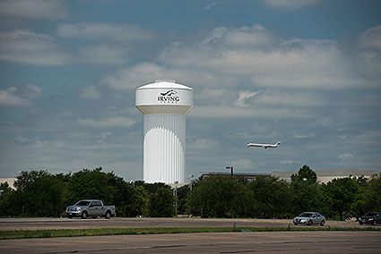 Irving, TX contains part of the Dallas/Fort Worth International Airport, so you can see airplanes depart and arrive the area and even pass the city's water tower at any time of the day.