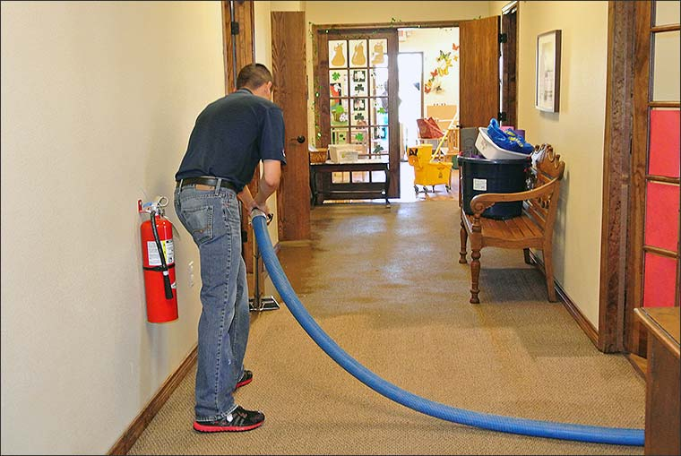 Restoration technician extracting water from carpet at a commercial property